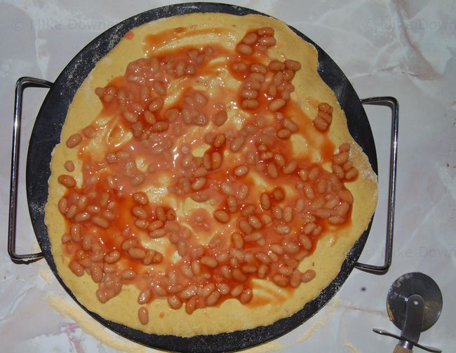 Baked bean pizza being assembled